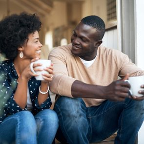 young couple talking and drinking coffee at home smiling