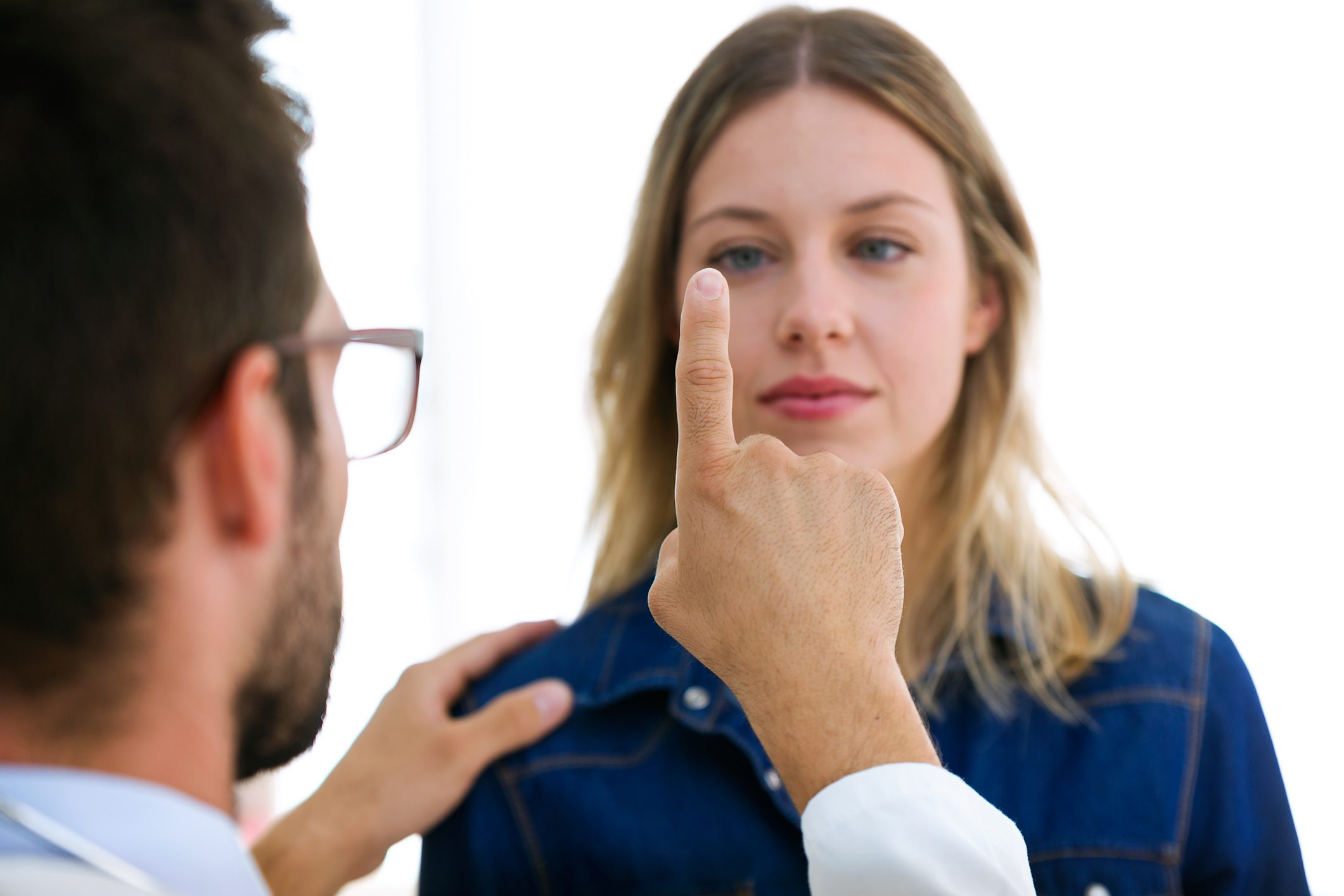 Attractive male doctor ophthalmologist checking the eye vision of beautiful young woman in modern clinic.