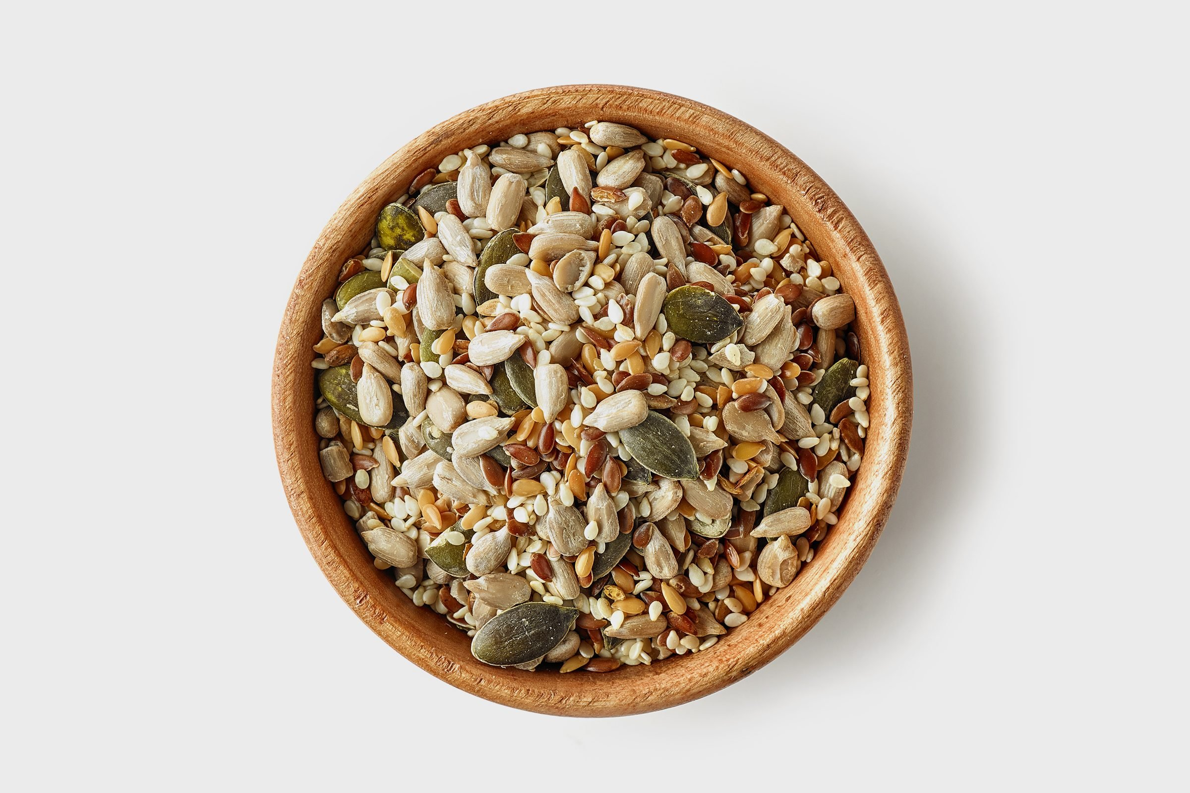 bowl of various seeds on white background