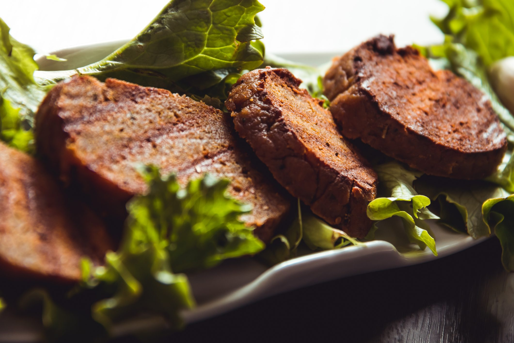 cooked seitan on bed of lettuce