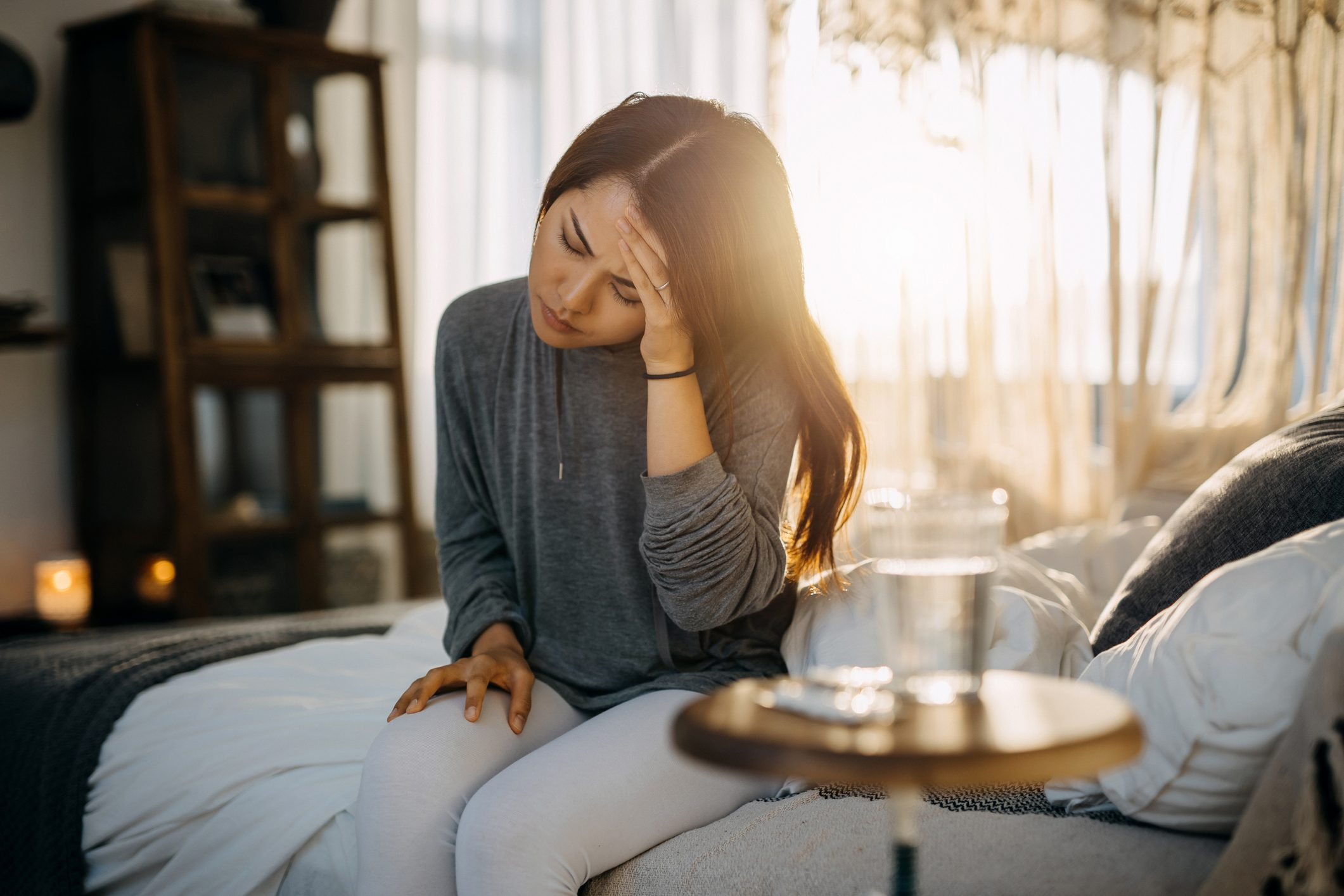 woman sitting in bed, holding her head