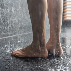 Legs of the girl standing under the shower under the stream of water, health beauty and hygiene concept