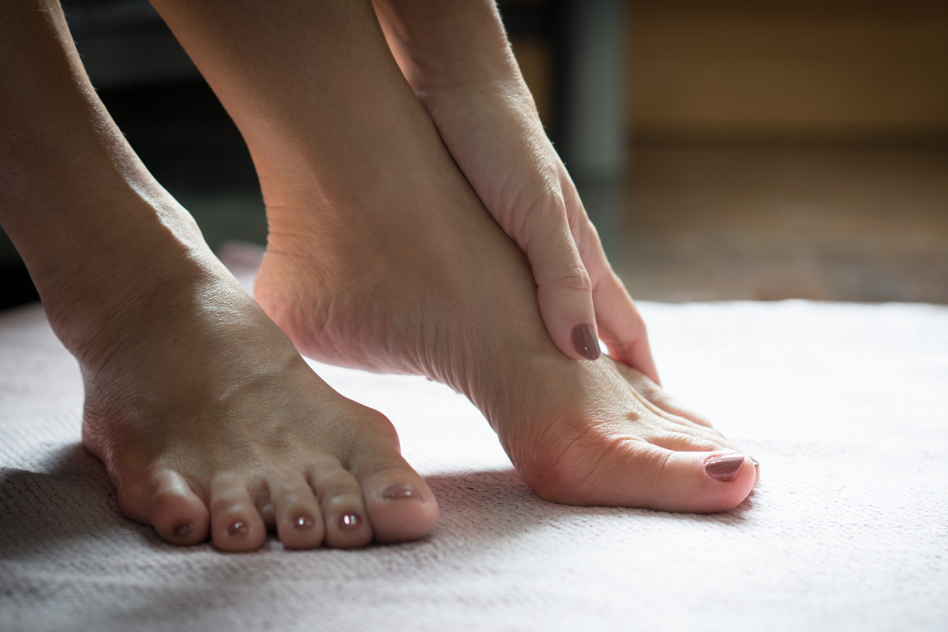 Bare feet of beautiful working woman resting her toes at home to release pain of her Bunions (Hallux valgus) toes