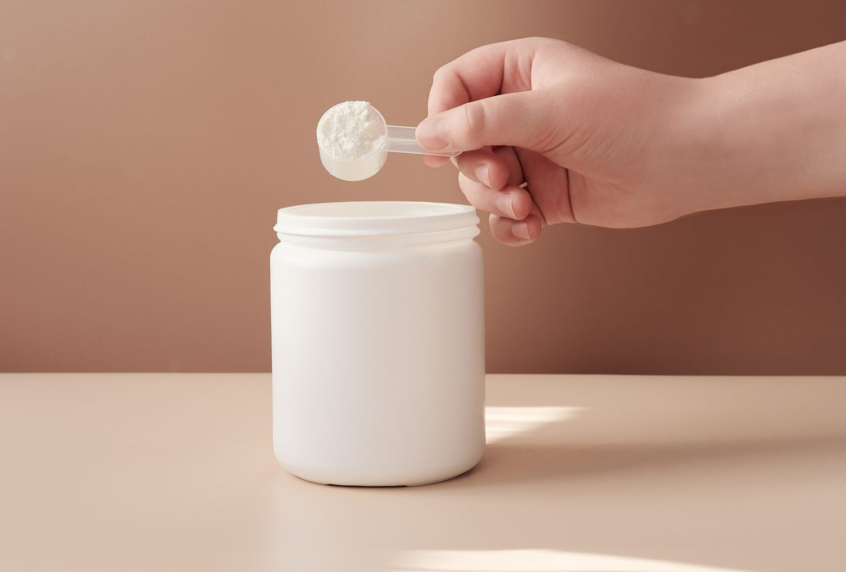 hand with scoop of powder from jar