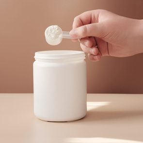 Cropped Hand Putting Coin In Jar On Table