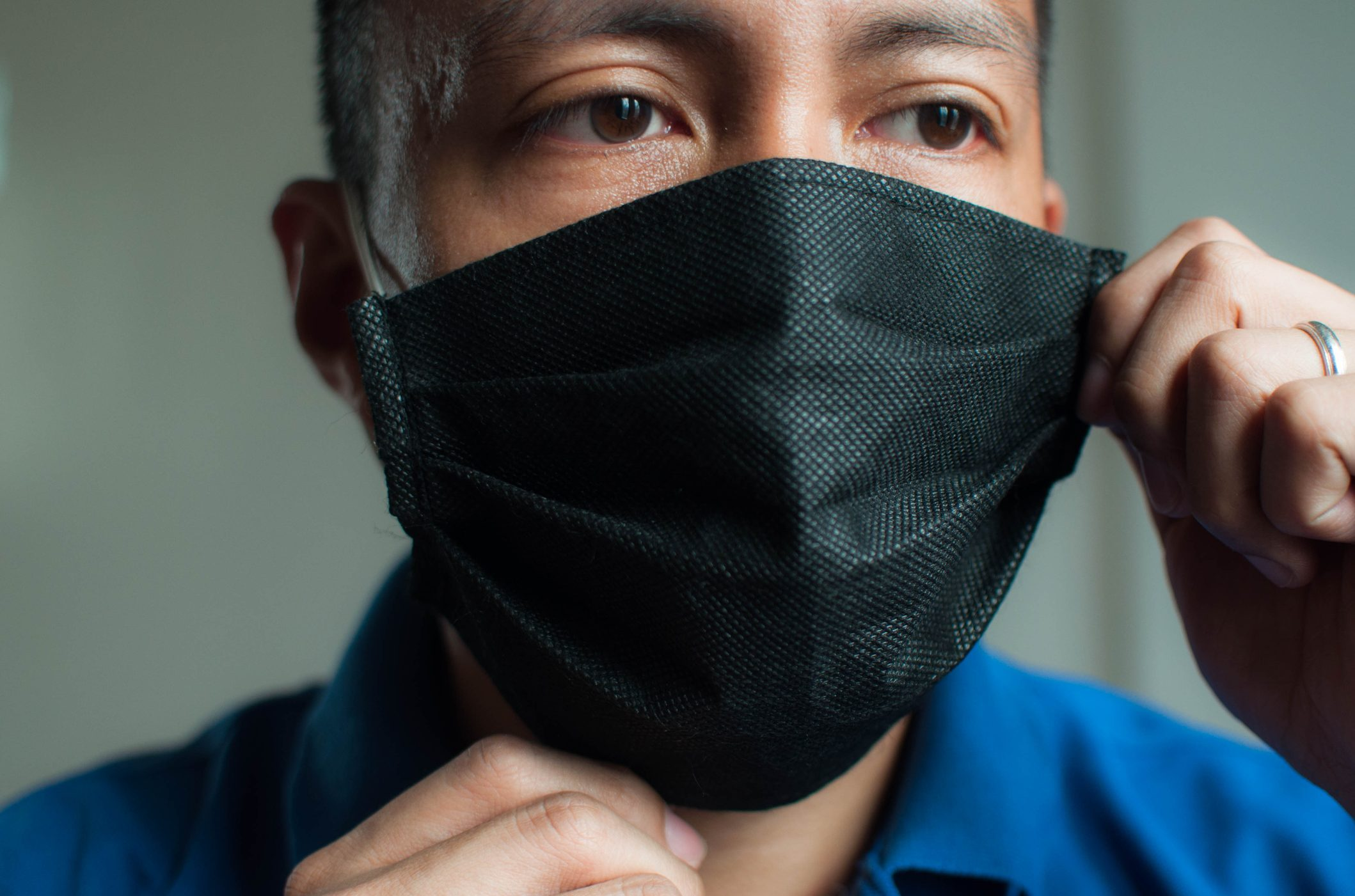 """A young Southeast Asian man is wearing a black protective face mask during the """"new normal"""" in coronavirus pandemic"""