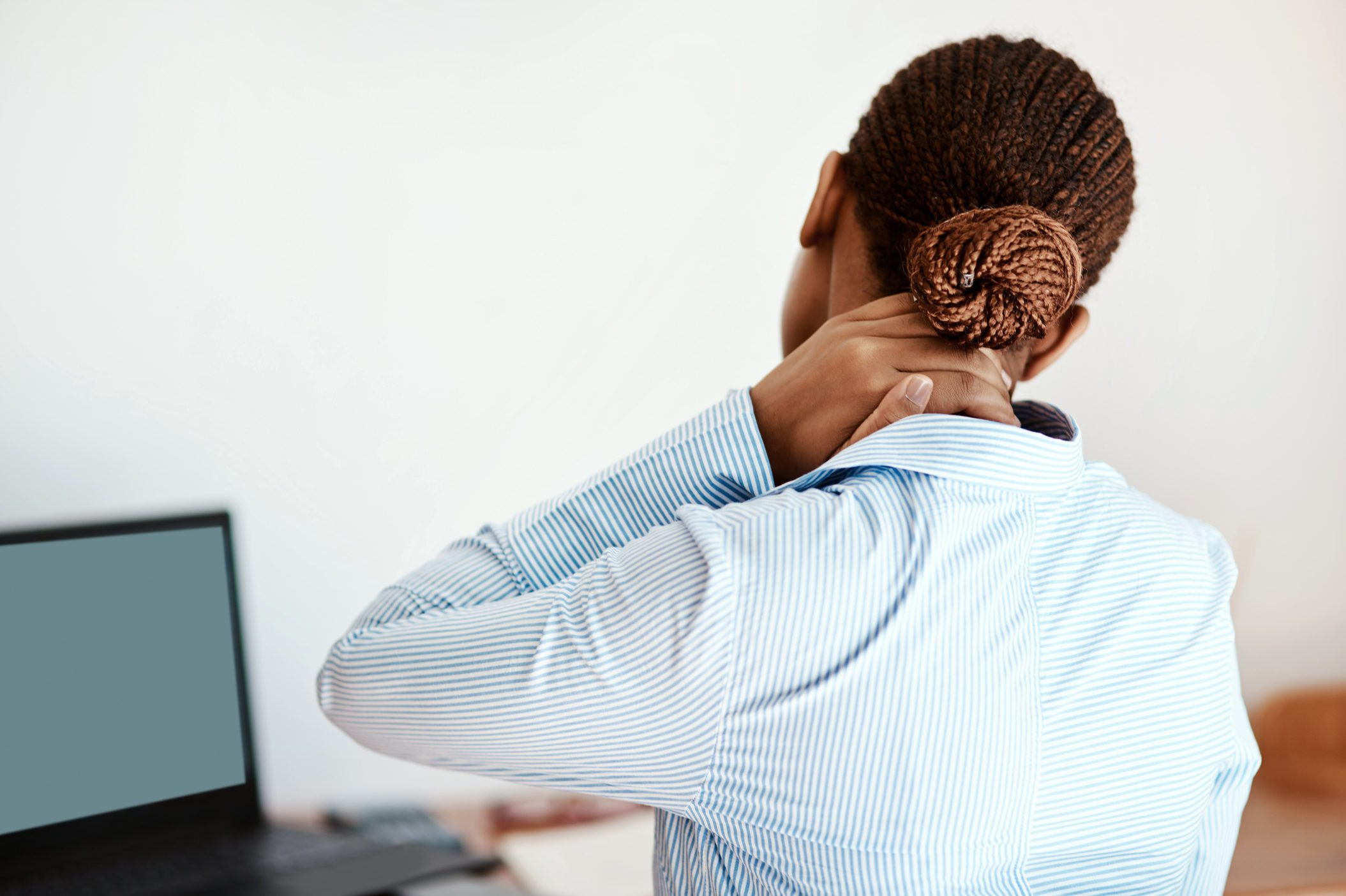 woman at computer with hand on her neck
