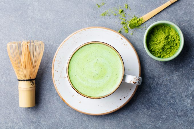 Matcha green tea latte in a cup with bamboo whisk. Top view.