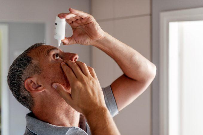 Mature Man Putting Eye Drops In Eyes
