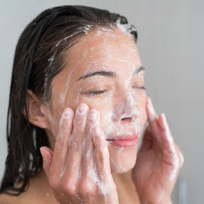 Skincare woman washing face in shower