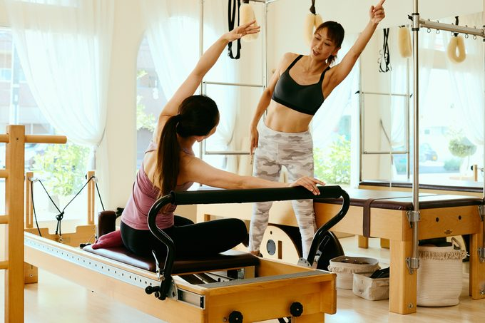 woman pilates instructor leading class on pilates reformers in fitness studio