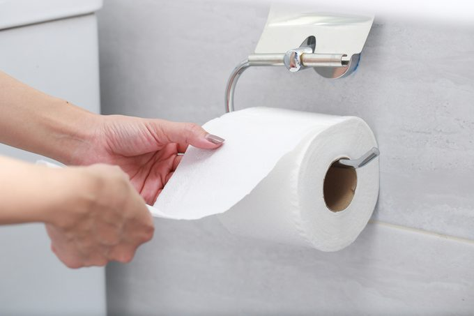 Cropped Hands Of Woman Holding Toilet Paper In Bathroom