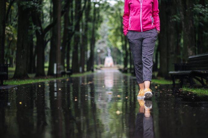 Carefree young woman enjoying relaxing walk after rain