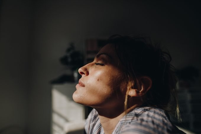 woman with eyes closed in the sunlight