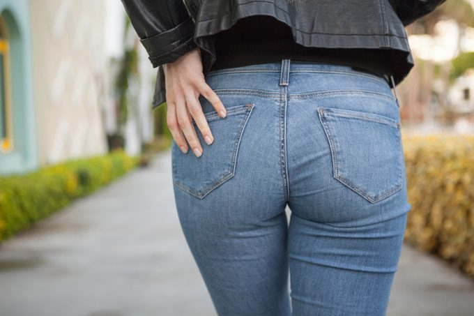 Rear View Of Woman Touching Jeans Pocket While Standing Outdoors
