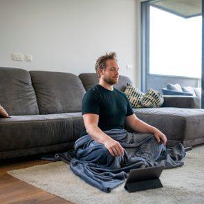 Caucasian Man Meditating Using Digital Tablet in the Living Room