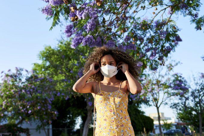 Woman outdoors putting on antiviral mask