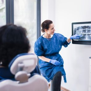 Dentist Explaining Tooth X-Rays To A Patient.