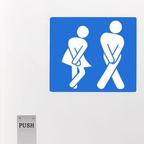 Gender neutral toilet sign, legs crossed urgent need to urinate