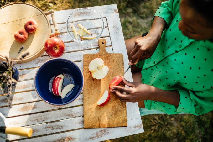 Woman Cutting Fruit Outdoors Preparing Snack For Family