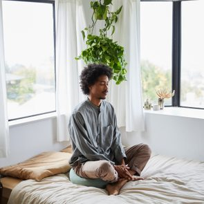 Young man sitting alone on his bed and meditating