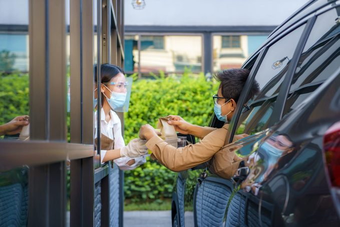 man in protective mask taking food bag and coffee with woman waitress wearing face mask and face shield at drive thru during coronavirus outbreak.