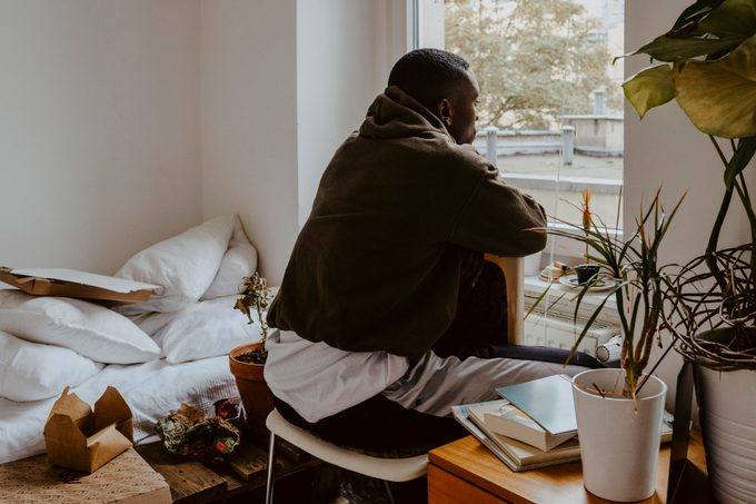 Rear view man looking through window while sitting in bedroom