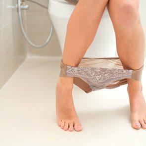 woman's legs while sitting on toilet