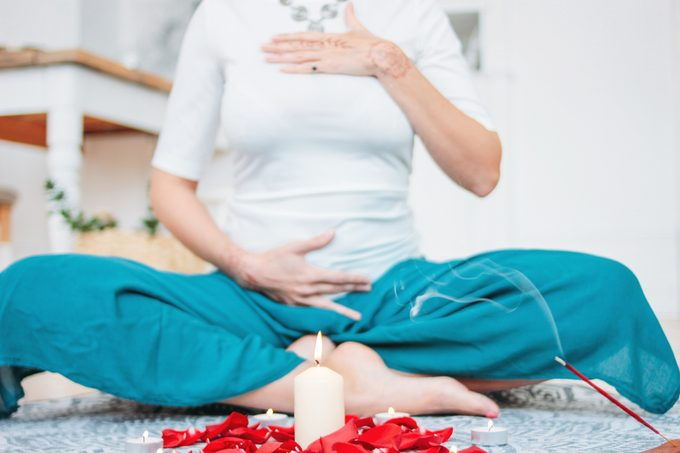 Woman in ethnic costume practicing yoga in front of candles and red rose petals, hands with mehendi on the heart chakra