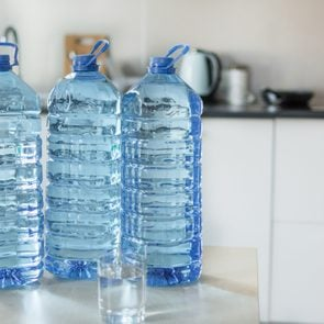 Big plastic bottle with water on the table over bright kitchen backgroung.