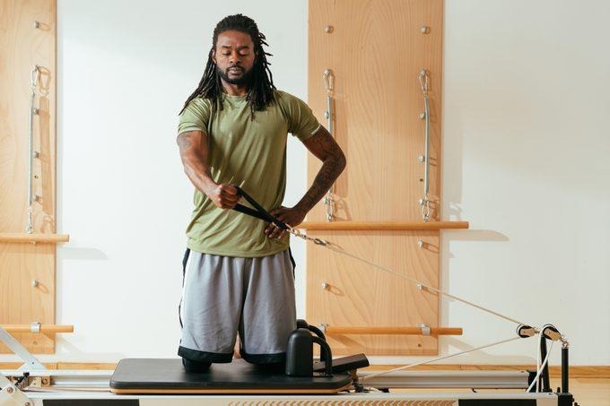 Sportsman Doing Reformer Pilates Exercise