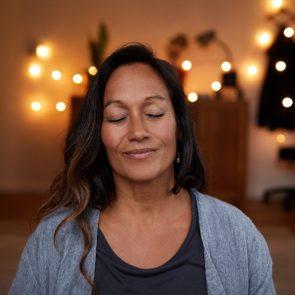 Serene mature woman smiling while meditating at home