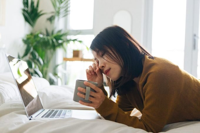 Young woman feeling tired when using laptop working from home
