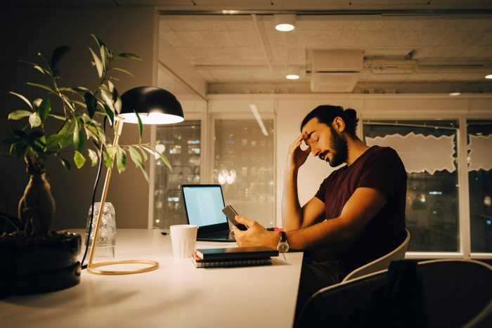 Exhausted businessman with head in hand working late at creative office