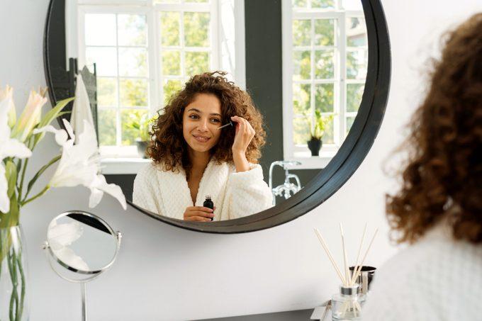 woman applying serum to face in bathroom mirror