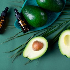 Avocado oil in dropper bottle and avocados on the green background
