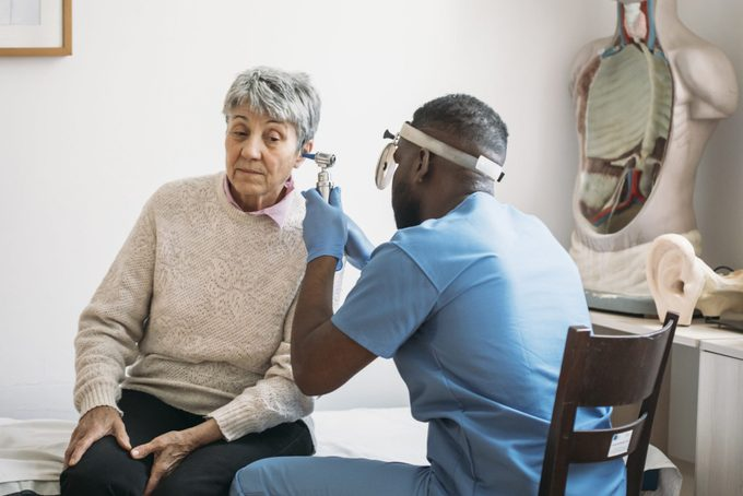 Mature adult woman has ears checked by doctor at routine medical appointment