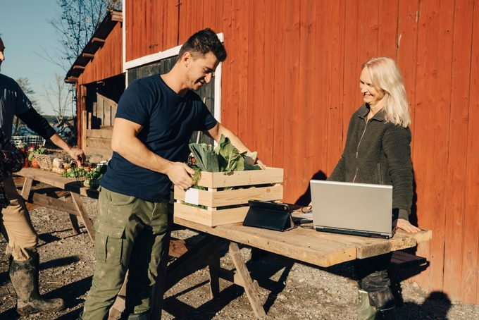 Mid adult man buying vegetables full of crate from female farmer at market