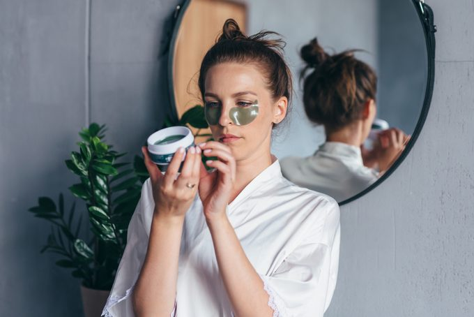 Woman Studies The Instructions For Using Eye Patches.