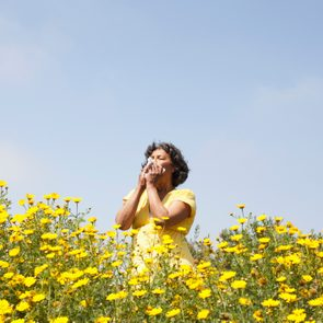 Mixed race woman in field of flowers enjoying scent