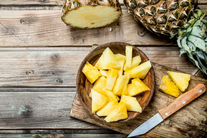 Pieces of fragrant pineapple in a bowl on a cutting Board with a knife.