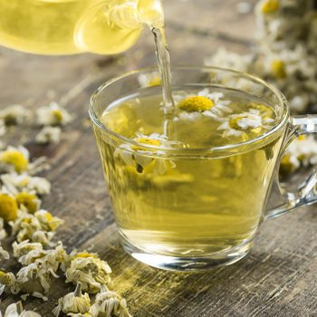 glass cup of chamomile tea with dry daisy flowers and teapot on rustic wooden background, herbal medicine hot drink concept
