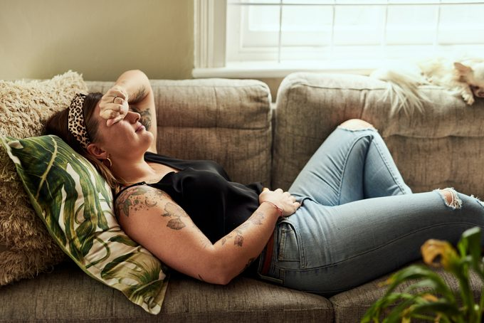 Shot of a young woman suffering from stomach cramps on the sofa at home