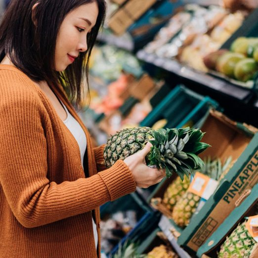 Young woman shopping for fruits and vegetables in grocery store