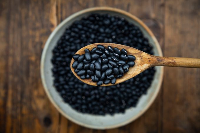 Overhead view of spoon and bowl of black bean on wooden table