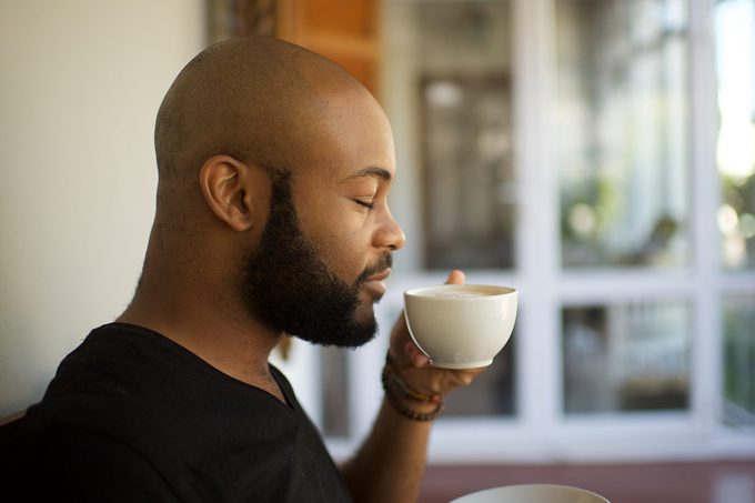Millennial man smelling coffee in a cup