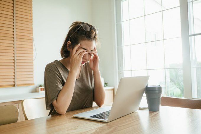 woman struggling with using laptop at home.