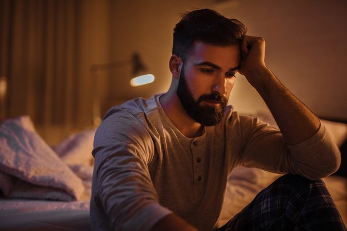 Depressed young man in his bedroom thinking about something
