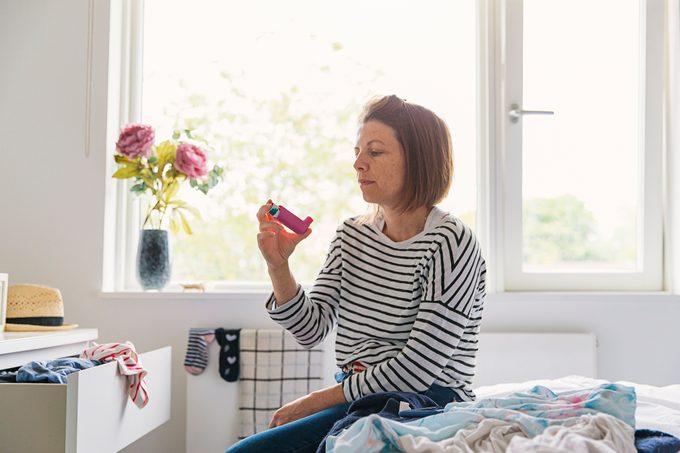 Woman with pink asthma inhaler
