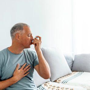 Mature man using asthma inhaler